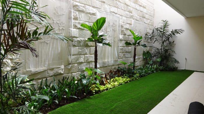 Desain Rumah Belakang dengan Rumput Persegi Panjang dan Tanaman Hias