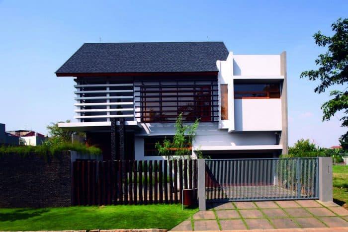 Desain Rumah Dua Lantai dengan Batu Alam di Bagian Tiang dan Area Depan